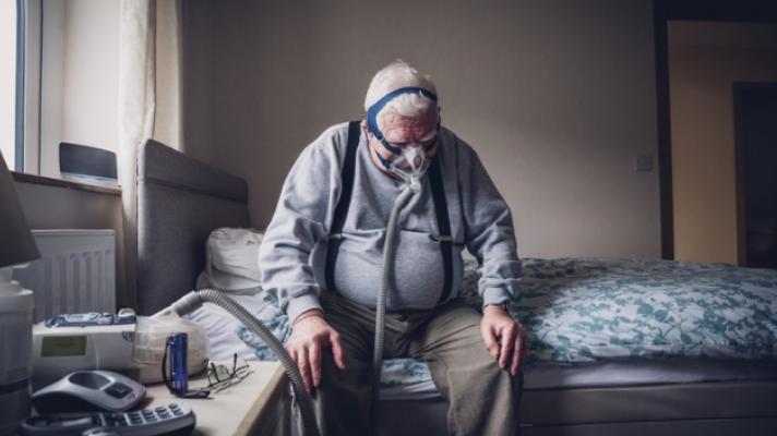 Senior man with oxygen mask.