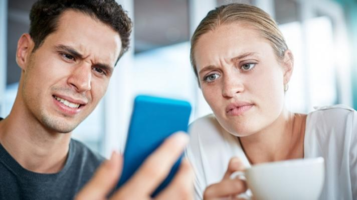 Irritated couple looking at cellphone.
