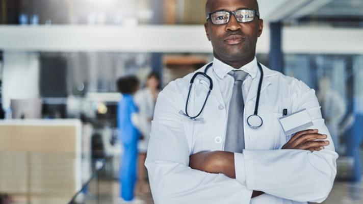 Doctor standing in busy hospital.