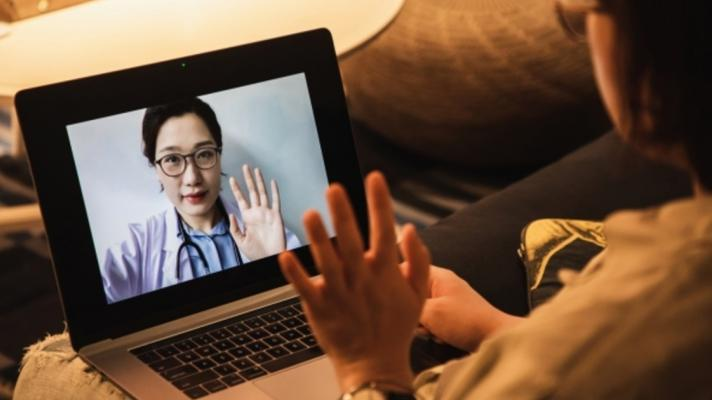 A person looks at a doctor on a screen