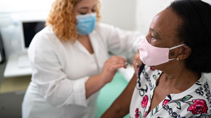 Nurse administers COVID-19 vaccine.