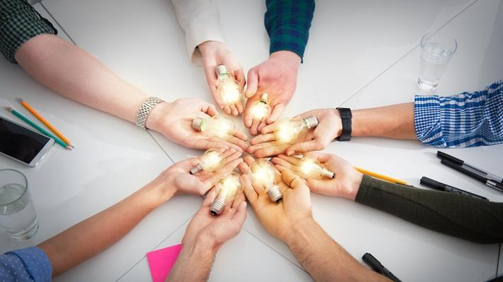 Circle of hands holding lightbulbs