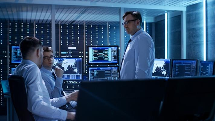 A meeting of people in a computer server room