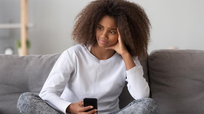 Upset woman holding smartphone
