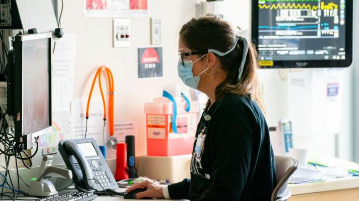 A healthcare provider in a mask enters data at a computer