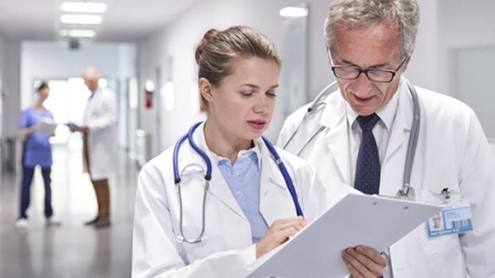 Doctors looking at clipboard.