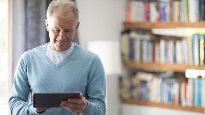 A person in a light blue sweater looking at a tablet