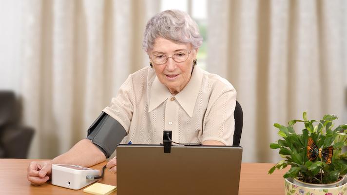 Senior using telemedicine blood pressure cuff.
