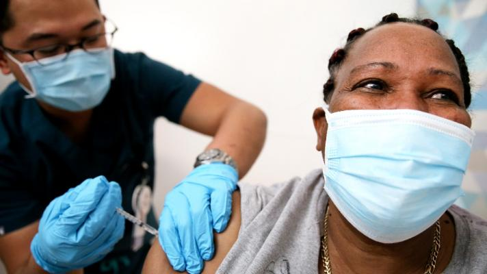 A person gets vaccinated by another person, both in masks