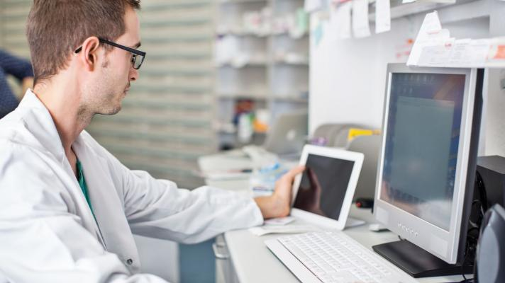 A pharmacist looking at a tablet and computer.