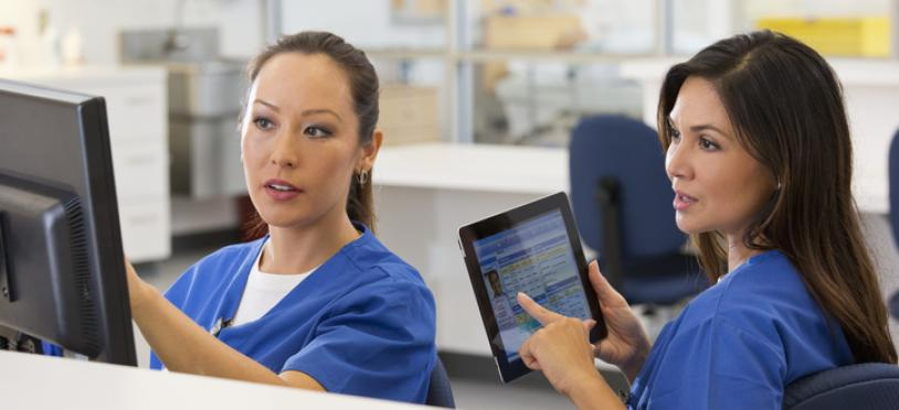 Healthcare worker with tablet looking at screen another worker is pointing at