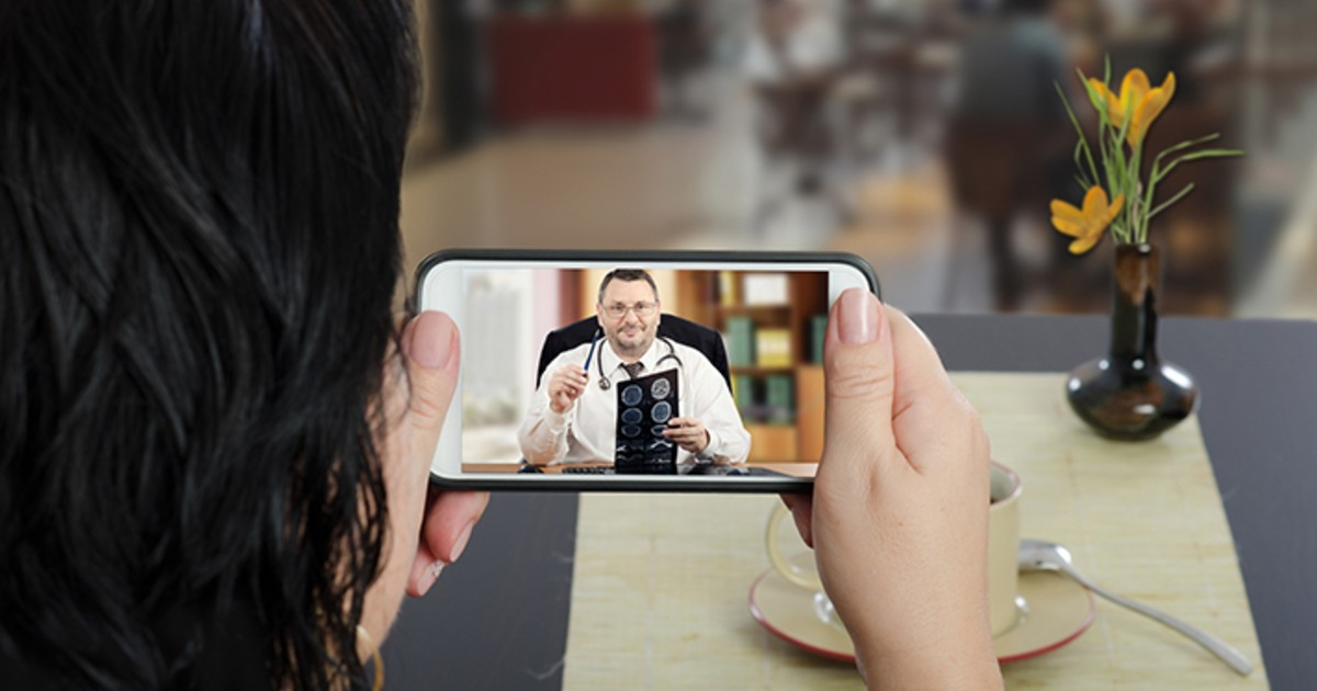 A patient looks at a doctor on a mobile phone screen